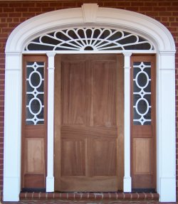 Therma-Tru door with sidelites, elliptical transom, custom Decralite™ grids, fluted pilasters, and a keyed arch.